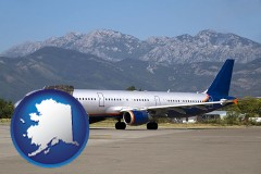 alaska commercial aircraft at an airport, with mountainous background