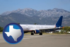 texas commercial aircraft at an airport, with mountainous background