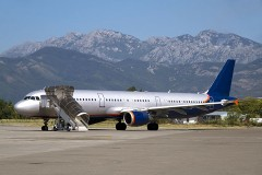commercial aircraft at an airport, with mountainous background