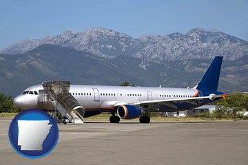commercial aircraft at an airport, with mountainous background - with Arkansas icon