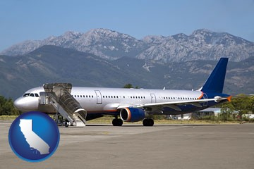 commercial aircraft at an airport, with mountainous background - with California icon