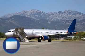 commercial aircraft at an airport, with mountainous background - with Colorado icon