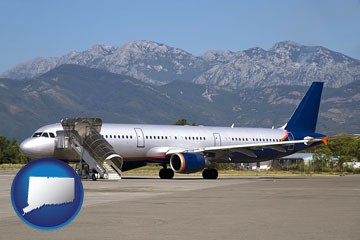 commercial aircraft at an airport, with mountainous background - with Connecticut icon