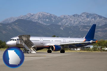 commercial aircraft at an airport, with mountainous background - with Georgia icon