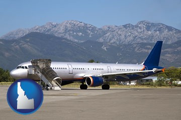 commercial aircraft at an airport, with mountainous background - with Idaho icon