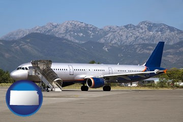 commercial aircraft at an airport, with mountainous background - with Kansas icon