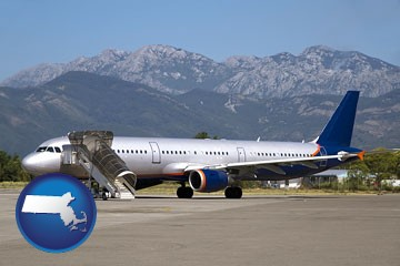 commercial aircraft at an airport, with mountainous background - with Massachusetts icon