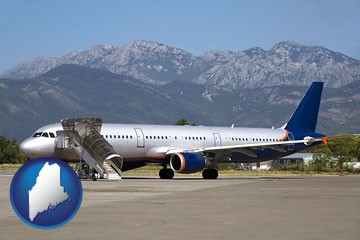 commercial aircraft at an airport, with mountainous background - with Maine icon