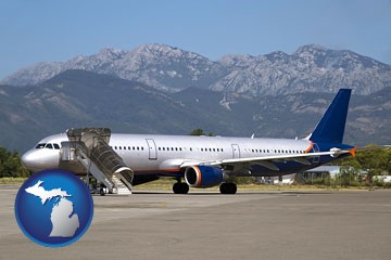 commercial aircraft at an airport, with mountainous background - with Michigan icon