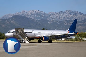 commercial aircraft at an airport, with mountainous background - with Minnesota icon