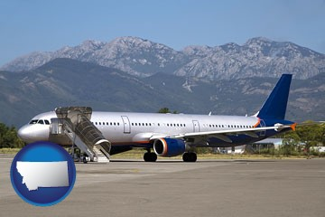 commercial aircraft at an airport, with mountainous background - with Montana icon