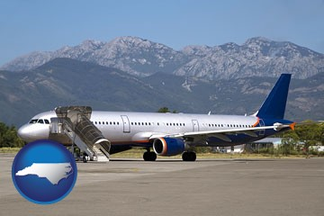 commercial aircraft at an airport, with mountainous background - with North Carolina icon