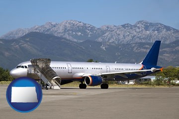 commercial aircraft at an airport, with mountainous background - with North Dakota icon