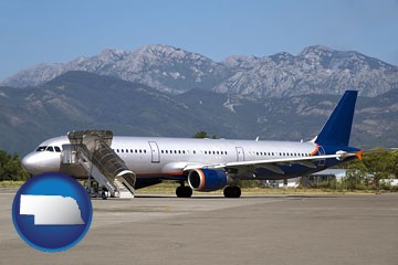 commercial aircraft at an airport, with mountainous background - with Nebraska icon