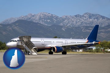 commercial aircraft at an airport, with mountainous background - with New Hampshire icon