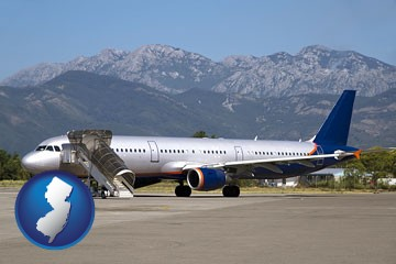 commercial aircraft at an airport, with mountainous background - with New Jersey icon
