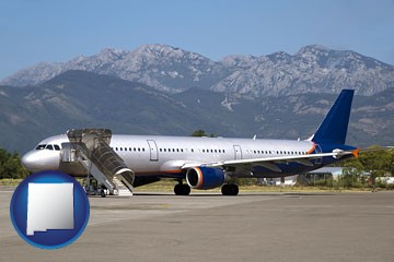 commercial aircraft at an airport, with mountainous background - with New Mexico icon