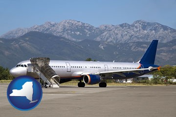 commercial aircraft at an airport, with mountainous background - with New York icon