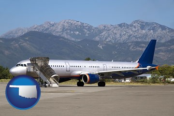 commercial aircraft at an airport, with mountainous background - with Oklahoma icon