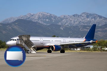 commercial aircraft at an airport, with mountainous background - with South Dakota icon