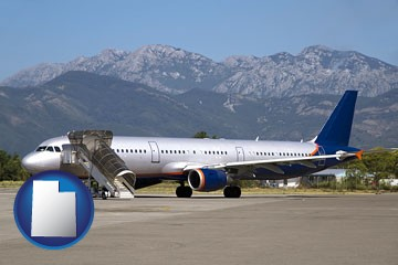 commercial aircraft at an airport, with mountainous background - with Utah icon