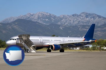 commercial aircraft at an airport, with mountainous background - with Washington icon