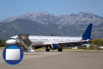 commercial aircraft at an airport, with mountainous background - with Wyoming icon