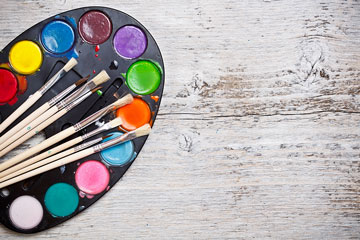 an artist palette and paintbrushes on a wooden board