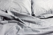 rumpled gray pillows and sheets on a bed
