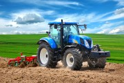 a blue farm tractor and a red cultivator