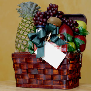 a gift basket with fruit, cheese, sausage, and preserves