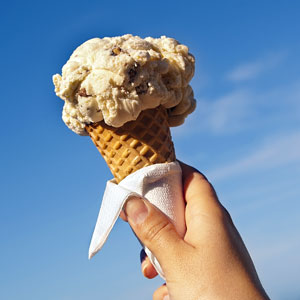 a hand holding an ice cream cone against a blue sky background