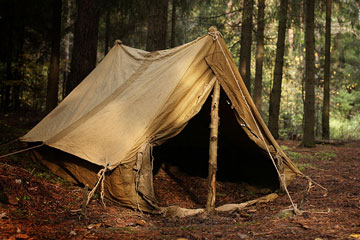 an old canvas tent in a forest