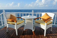 white, outdoor wicker furniture on an oceanfront deck