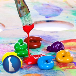 colorful oil paints and paintbrush - with Delaware icon