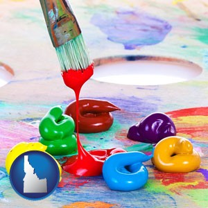 colorful oil paints and paintbrush - with Idaho icon