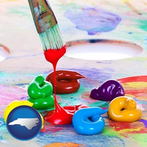 colorful oil paints and paintbrush - with North Carolina icon