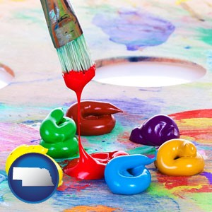 colorful oil paints and paintbrush - with Nebraska icon