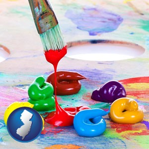 colorful oil paints and paintbrush - with New Jersey icon