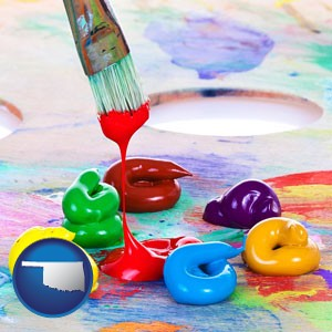 colorful oil paints and paintbrush - with Oklahoma icon
