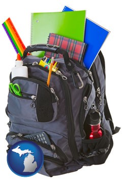 a backpack filled with school supplies - with Michigan icon