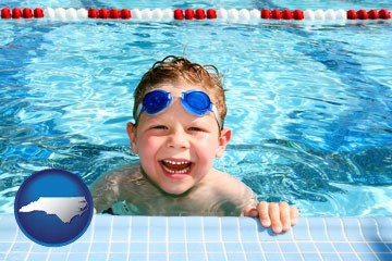 a boy in a swimming pool - with North Carolina icon