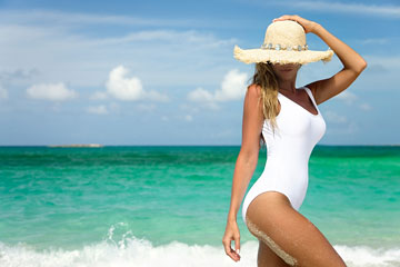 a woman wearing a white, one-piece swimsuit