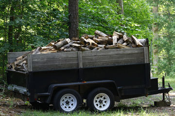 a utility trailer filled with firewood logs